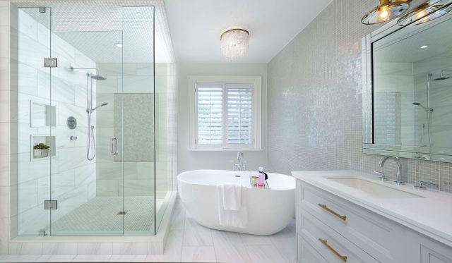 This master bathroom exudes contemporary elegance! Here's what we did to create an award-winning space that feels equal parts feminine and sophisticated! ⠀ ⠀ ▪️We added some visual interest with the mini glass tiles to create a pearlescent look. Tiles are great because they protect your walls from water damage and toothpaste smudges alike.  ⠀ ▪️We chose a light grey colour for the vanity and for the faucets and hardware we mixed the metals, chrome, brass and polished nickel.   What would you like in your dream master bathroom? Let me know in the comments below 👇 .⠀ .⠀ .⠀ .⠀ #dvirainteriors #torontodesigner #interiordesign #luxurybathroom #luxurydesign #glasstiles #miniglasstile #oldworldbathroom #charmingbathroom #charmingbath #mosaictile #contemporarybathroom #bathroomtile #interiorstyle #awardwinning #torontointerior #pearltile #whitetile #greyvanity #goldaccents #goldbathroom #silverfaucet #brassfaucet