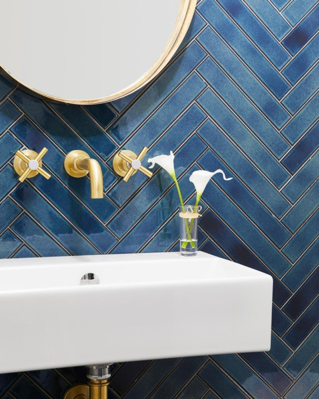 There's nothing I love quite more than adding the perfect tile to a powder room!   We've talked about wallpaper before, but tile is the unsung hero of small spaces like powder rooms. It adds depth and lavishness, especially when paired with the neutral white and gold tones to tie it all together.   We added an upward herringbone pattern to the vanity wall and decorated with gold faucets for a glittering, jewel-like effect. The gold elements around the mirror contrasting with the eye-catching blue is to die for! 🤩⠀ ⠀ Femininity and masculinity make for a fine balance in this powder room- how do you think we did?! 💎⠀ .⠀ .⠀ . . . . . . #dvirainteriors #powderroom #bathroomdesign #bathroominterior #interiordesignblog #housegoals #dreamhome  #herringbonetile #interiordesign #torontohomes #housegoals #homesweethome #dreamhome #customhome #torontointeriordesign #goldelements #goldbathroom #bluebathroom #bluetiles #bluepowderroom
