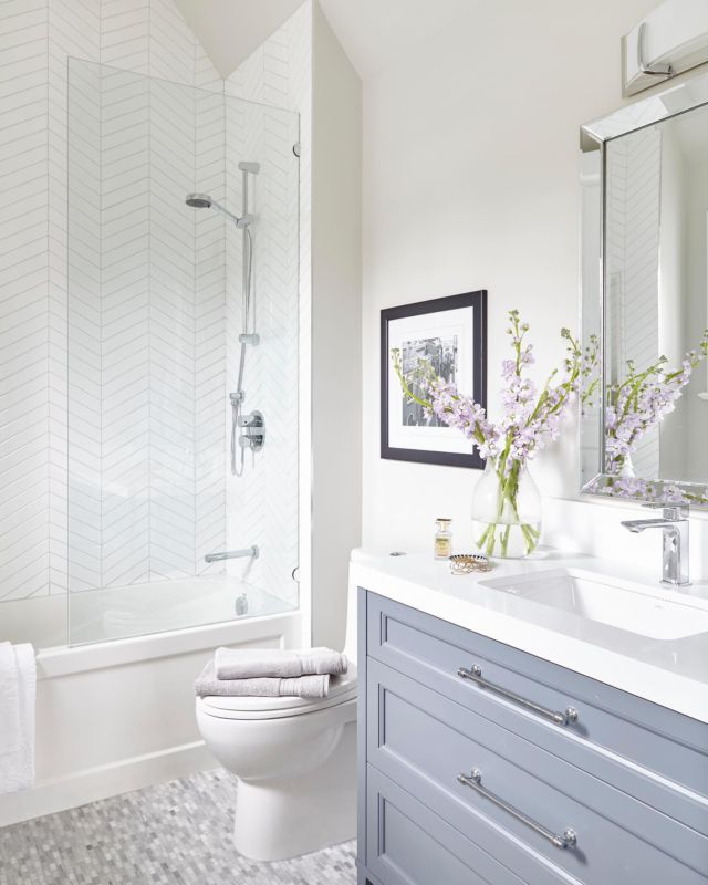 The gorgeous use of herringbone in this master bathroom shower coincides with the unique angular dimensions of the wall. It draws your eye up toward this skylight, which is apt for this dreamy cloudlike nature of this space.   Further depth is added with the grey tones and silver accents incorporated, and it's primed to add pops of colour of your choosing, much like the gorgeous fresh-cut flowers! . . . . . . . . #dvirainteriors #bathroomrenovation #luxuriousbathroom #luxurybathroom #spalikebathroom #spabathroom #myhousebeautiful #interiorinspo #inspiremeinterior #luxuryinteriors #worldofinteriors #luxeinteriors #bathroomvanity #bathroomescape #bathroomdecoration #bathroominterior #bathroominspiration #bathroominspo #bathroomgoals #bathroomstyling #bathroomdesigns #dreambathroom #herringbonetile #whitebathroom #greytones #skylightinspo #torontointeriordesign #torontodesign #dreambathroom