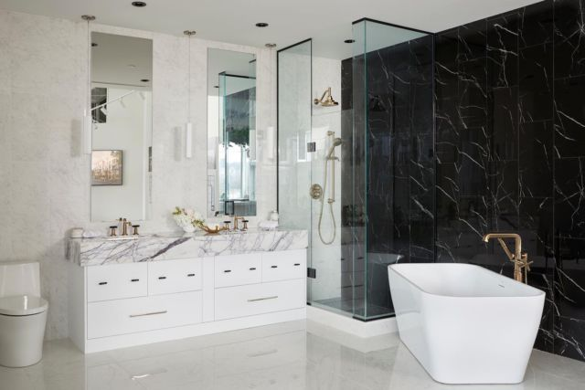 For this bathroom, we went with a combination of high-end and budget-friendly materials to create a contemporary contrasted look in the space!  When picking materials and finishes for a bathroom renovation you may notice that there are so many options available. The abundant selection of stones, tiles, and finishes can be overwhelming! But if you work with a designer you can be confident that you'll get the best look, prices, and advice! ⠀ Here's how we created a high-end contemporary look using a combination of high end and budget-friendly materials👇  ◾️We went with black porcelain shower tiles that have the look of real marble. We went with porcelain because it is durable and low maintenance. These tiles are timeless and evoke a contemporary feel.   ◾️In order to give our vanity an upgraded look, I chose a gorgeous countertop with a thick profile to it. To accent the bathroom we went brass finishes that contrast well against our finishes.  We hope you love the @staffordhomes store bathroom vignette project as much as we do!  . . . . . . . . #dvirainteriors #stafford #commercialdesign #showroomreveal #storereveal #bathroomdesign #masterbathroom #bathroomdesign #bathroomreno #luxuriousbathrooms #stonewall #luxuriousbathroom #naturalstone #bathroominspo #masterbathroom #bathroomremodel #masterbath #masterbedroom #bathroominspo #bathroomgoals #bathroomideas #bathroomsofinsta #bathroomdecor #bathroomvanity  #bathtubgoals #freestandingbath #freestandingtub #soakingtub #spabathroom #spabath  
