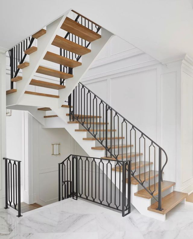 A well-designed staircase can create a grand welcome at the entryway! ⠀⠀ Pictured here is one of my favourite stairs to date! We love the stunning iron railing and how it stands out against the light wood treads and white walls! To give the space an opulent look we installed detailed millwork and crown molding on the main and top floor!   You can view more staircase projects that were part of larger home projects, on my website. www.dvira.com⠀  .⠀⠀ .⠀⠀ .⠀⠀ .⠀⠀ .⠀⠀ .⠀⠀ #dvirainteriors #luxurylifestyle #frontentry #torontointeriors #frontentrance #interiorsofinstagram #staircaseproject #interiorvibes #luxurydesign #luxuryinteriors #designerofluxury #homeluxury #vaughan #kleinburg #staircaserenovation #staircasereno #luxuryhomes #kleinburg #mansion #mansiondesign #interiors #interiordesign #mystylishspace #stairbanister #stairtread #handrails #stairfloors #stairsathome #homeinspiration  #staircase