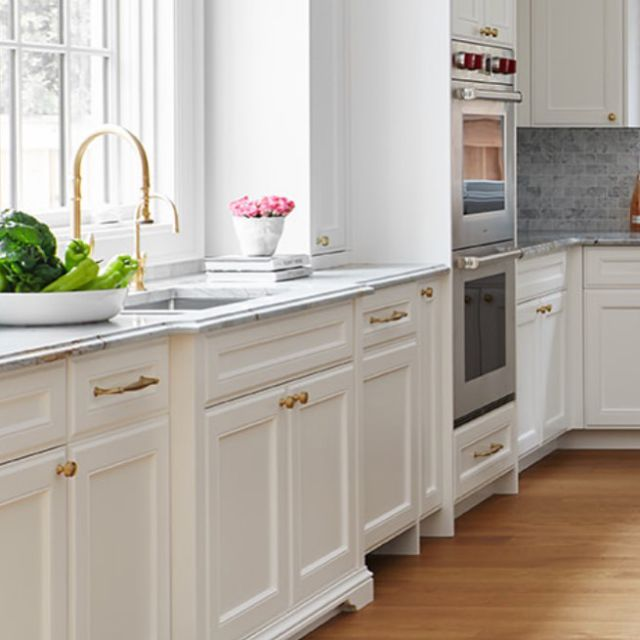 We pushed the design boundaries in this kitchen!  This kitchen was part of a larger custom home project in Kleinburg, Ontario! The style of the homeowner's previous kitchen was very dark and traditional. But for their new custom home, they were looking for a fresh lighter classic spin for the style of the kitchen.   For the design, we used fresh, bright, and light materials for the flooring, windows, and cabinets. We outfitted the cabinets with classic moldings and decorated them with high-quality hardware from @waterstreetbrass . . . . . . . . #dvirainteriors #torontokitchen #torontodesigners #torontointeriordesign #classickitchen #whitekitchen #kitchensofinstagram #kitchensofinsta  #kitchenisland #kitchencabinets #kitchencabinetry #kitchencabinet #brightkitchen #lightflooring #oakfloors #oakflooring #classicmoldings #kitchendecor #customcabinetry #kitchenlighting #kitchenstyle #customcabinets #kitchensink #kitchens #kitcheninterior #interiordesign