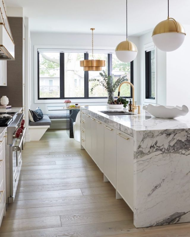 The white cabinets and marble countertops not only differentiate the kitchen area in this open floor plan, but they also add a level of sophistication and warmth to the space.   The owners of this custom home dreamed of a contemporary yet bold kitchen. Here's how we pulled off the look in this kitchen while keeping function and durability top of mind 👇⠀ ⠀⠀ We chose to outfit all counter and wall surfaces in a white tone, creating a chic and open feeling space. We added a few decorative elements such as details on the cabinets and on the hood range. This creates a more glamorous and classic look.  ⠀⠀⠀ ⠀⠀⠀ We installed a waterfall Island that we outfitted with marble with deep veining. I love using waterfall Islands in open-concept spaces as they are stunning focal points, stylish seating areas, and protect the kitchen cabinets. ⠀⠀  Project- Ava www.dvira.com/galleries/ava .⠀⠀⠀ .⠀ . ⠀⠀ .⠀⠀⠀ #dvirainteriors #newhomedesign #ontariohomes #waterfallisland #whitecabinet #whitekitchen #designerlife #luxurykitchen #homedesign #newbuild #newconstruction #foresthill #stylishseating #housedesign #sophisticatedkitchen #marbleisland #housedesigner #kitchencabinets #modernkitchen #newhome #newhomeowner #interiordesign #designerlifestyle #customhome #waterfallisland  #whitecabinets #whitekitchen #luxuryhomes #torontomansion