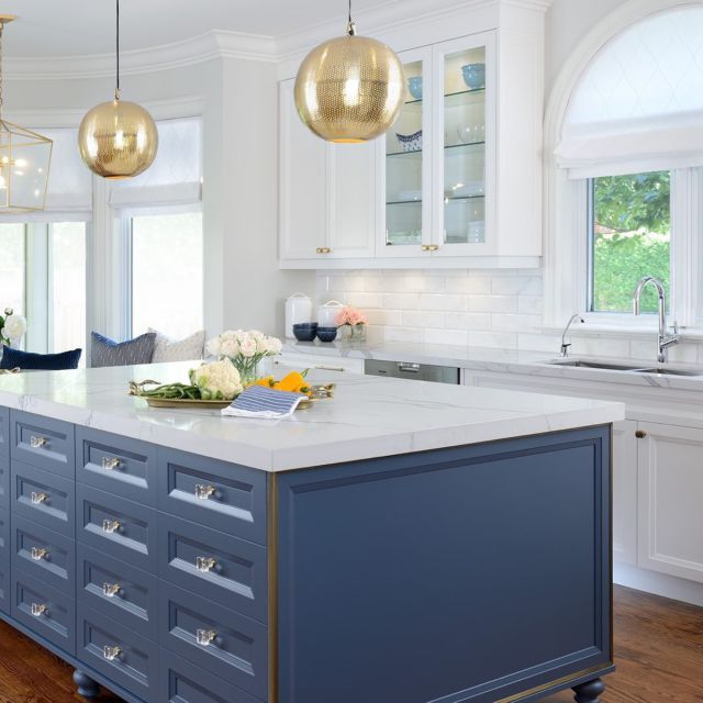 Contemporary reigns supreme  The kitchen island isn't just a place for guests to gather around, it also acts as a barrier to keep people out of the cooking area! We outfitted the island with Calcutta marble, custom cabinets dressed in blue and decorated with glass hardware! For a glittering metallic effect, we outlined the edge of the island with custom gold leaf.⠀  Having a dedicated breakfast area in the kitchen is perfect for a large family!  For the breakfast area we considered a variety of seating options, and in the end opted for a combination of custom bench and antique chairs.   Project- Ledbury Park To view more photos from this project visit our website www.dvira.com  . . . . . . . #kitcheninspo #architecture_hunter #passion4interior #dream_interiors #modernluxury #torontohomes #beautifulkitchen #luxuryinterior #kitcheninspo #marblekitchen #marblebacksplash #torontohome #earthykitchen #breakfastarea #marblecountertop #torontoliving #goldkitchen #classickitchen #bluekitchen #ornatekitchen #torontinteriordesign #kitchenoffices #kitcheninteriordesign #bluehood #bluekitchenhood #calcuttamarble #myhouseandhome #myhouseidea  #luxurykitchen