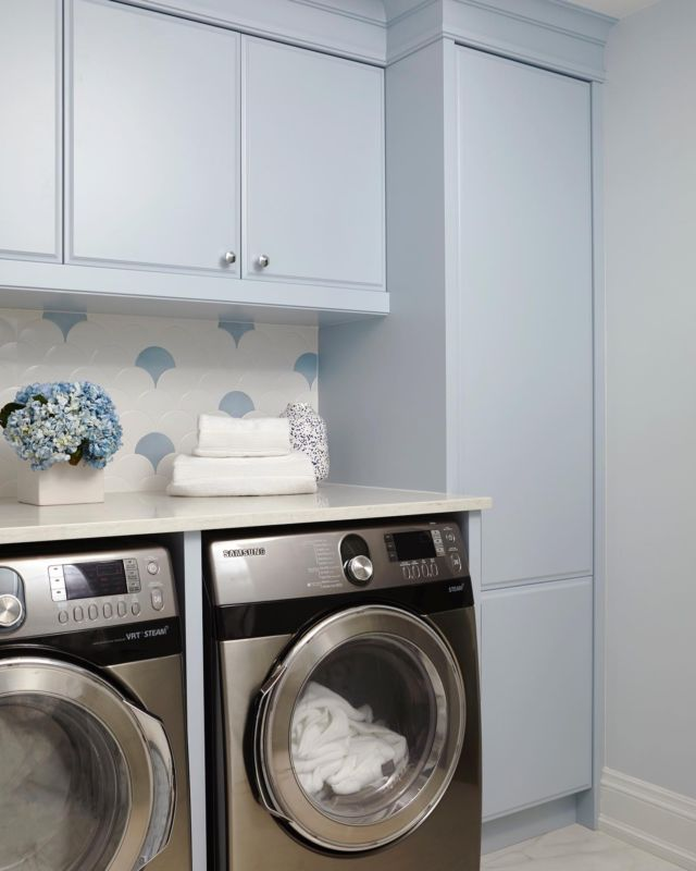 Over at custom home project Armour, we achieved the look of a cool, clean feeling laundry room that would inspire even the laziest person to do even more chores. Isn't that what every parent wants ;)⠀ ⠀ To give life and style to this space that's located in the basement we used elements such as   -Patterned accent wall with fan shaped tiling to make this small laundry room feel more fun and open.⠀ -The pastel blue colour with a cool undertone that adds a bit of happy energy to the space.⠀ -Durable marble-like flooring, made out of durable material, that's perfect for this busy high traffic area. ⠀ -Smart storage solutions in the form of closed cabinets all around the room. ⠀ -Large and energy-efficient front loading washer and dryer that is stacked beneath the raised white stone countertops.⠀ ⠀ Put all those elements together and the result is a beautiful and chic laundry room that's a standout space you'll want to show off to guests.⠀ ⠀ Save this post if you're looking to give your laundry room a bit of an upgrade! ⠀  Project- Armour  With the help of an interior designer, the laundry room can be just as stylish and functional as the rest of the house.   Are you looking to create your dream home? Ensure the careful smart planning you need from day one, and contact Dvira Interiors!   We look forward to incorporating our vision, scope, technical expertise, and industry connections to make your home's design/build experience as positive and rewarding as possible.⠀  www.dvira.com . . . . . . . . #dviraovadia #torontodesigner #interiordesign  #interiorinspo #interiorstyle #interiorinspiration #modern_homestyle #utilityroom #organizedmom #interiordesigner #getorganized #mudroomvibes #homeinteriors #stayorganized #laundryroom #laundrygoals #laundryroom #bluelaundryroom #bluecabinets #laundryroommakeover #laundryroomdecor #laundryday #farmhousedesignsinc #farmhouseinspired #farmhousechic #homeandgarden #farmhousedesign #modernfarmhouse #laundryroommakeover #interiordesign 