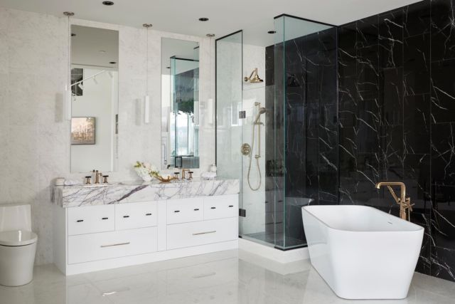 STUNNING. There is no better way to encapsulate the beauty of the marbling in this bathroom. There is a continuous flow as the black and creamy white mirror each other with the complimentary veining in their patterns. The round edging of the tub and toilet relax the space a little, which otherwise has quite angular aspects. The gold hardware seen throughout encapsulates the luxury perfectly of this bath.  Project- Stafford Sales Office  You can view more photos from this project on our website 👇 www.dvira.com/galleries/stafford-sales-office  Are you looking to create your dream home? Ensure the careful smart planning you need from day one, and contact Dvira Interiors! www.dvira.com  We look forward to incorporating our vision, scope, technical expertise, and industry connections to make your home's design/build experience as positive and rewarding as possible. . . . . . . #dvirainteriors #newhomedesign #ontariohomes  #designerlife #luxurykitchen #homedesign #newbuild #newconstruction #housedesign #sophisticatedbathroom #marblebathroom #housedesigner #newhome #newhomeowner #designerlifestyle #customhome #whitebathroom #luxuryhomes #torontomansion #stafford #masterbathroom #luxuriousbathrooms #stonewall #luxuriousbathroom #naturalstone #bathroominspo #masterbathroom #commercialdesign 