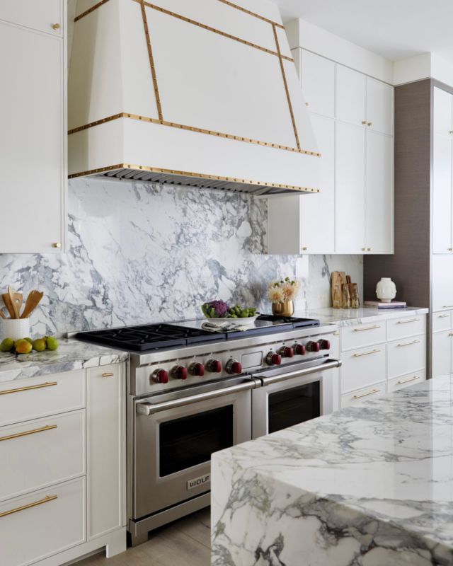 The simple glam of this range hood is an ideal match for the gorgeous marble backsplash, really allowing it to take center stage!  The golden details on the custom range match the hardware, yet don't overpower so that the stone with deep black veining can pop. A contemporary and fresh approach to this design was achieved.   Learn more about project Ava on our website 👇 www.dvira.com/galleries/ava  Are you looking to create your dream home? Ensure the careful smart planning you need from day one, and contact Dvira Interiors!   www.dvira.com  We look forward to incorporating our vision, scope, technical expertise, and industry connections to make your home's design/build experience as positive and rewarding as possible. . . . . . . . . #dvirainteriors #torontointeriordesign #kitchendesign  #luxuryhomes #torontomansion #newhomedesign #ontariohomes #newhomeowner #dayinthelife #interiordesign #designerlifestyle #designerlife #newconstruction #whitekitchen #brasshardware #goldhardware #goldfinishes #luxuryhome #kitchenstyle #modernkitchen #whitekitchens #kitchenstove #kitchenappliances #kitchenlover #kitchentrends #luxuryhomes #stainlesssteelhood #waterfallisland #whitecabinets